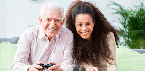 old man holding game console beside him is the caregiver