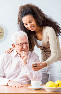 caregiver showing her smartphone to the old man