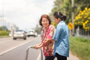 caregiver assisting old woman crossing the street